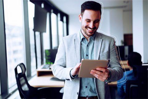 Ein Mann im Büro der ein Tablet in der Hand hält. | eggheads.net