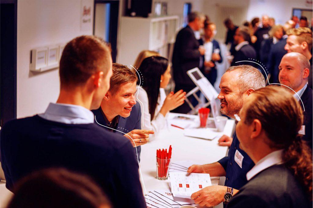 Fröhliche Menschengruppe lehnt an weißem Tisch mit vielen Menschen im Hintergrund   eggheads.net