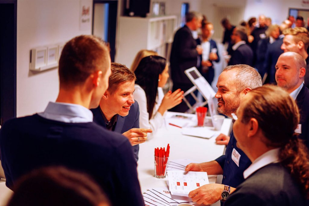 Cheerful group of people leaning against a white table with many people in the background during eggheads day   eggheads.net