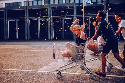 Konfetti fällt auf fröhliche Menschen bei Einkaufswagen-Rennen | eggheads.net