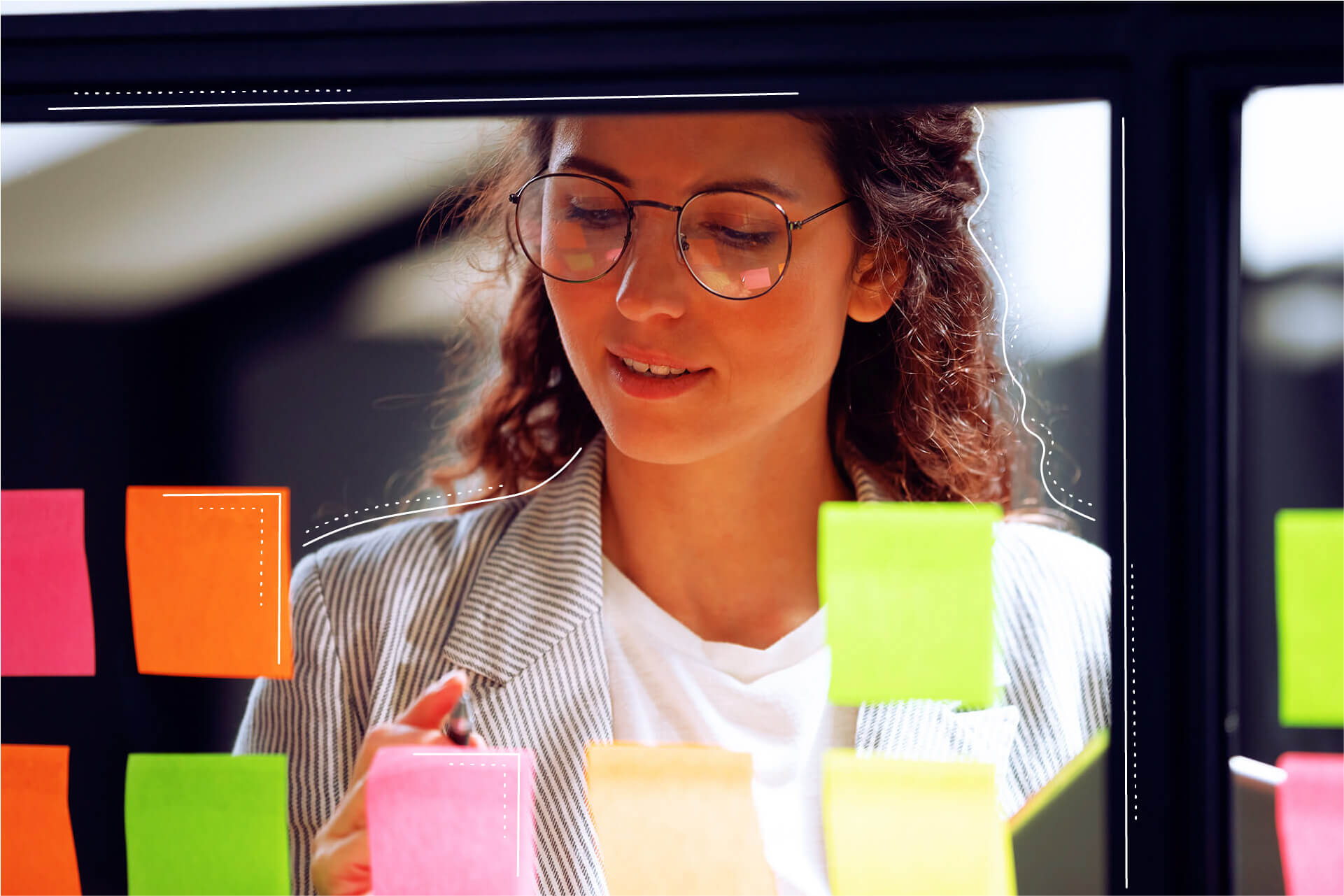 Woman sticking post-it notes on glass pane | eggheads.net