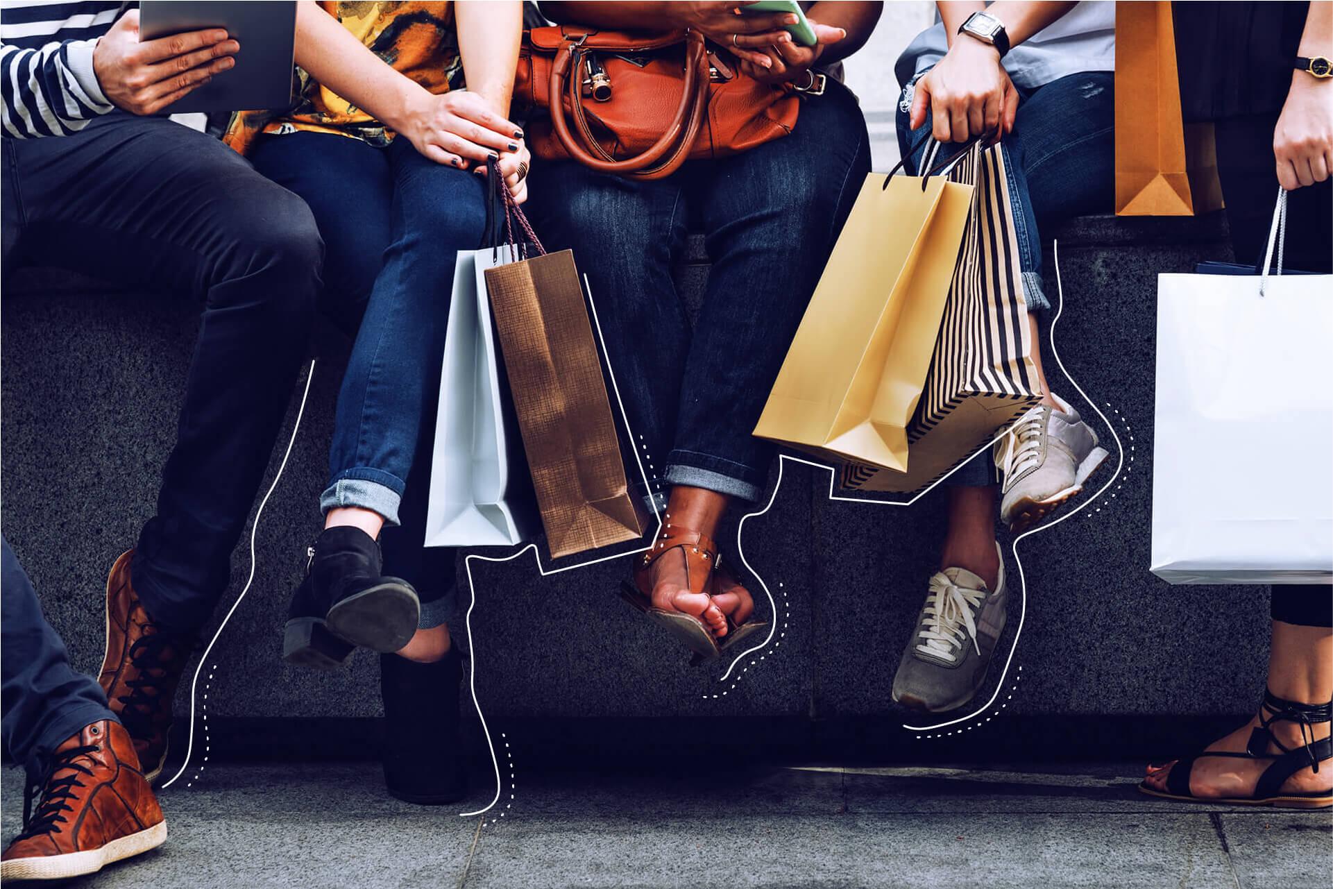 Menschengruppe mit Einkaufstaschen lässt die Füße baumeln | eggheads.net
