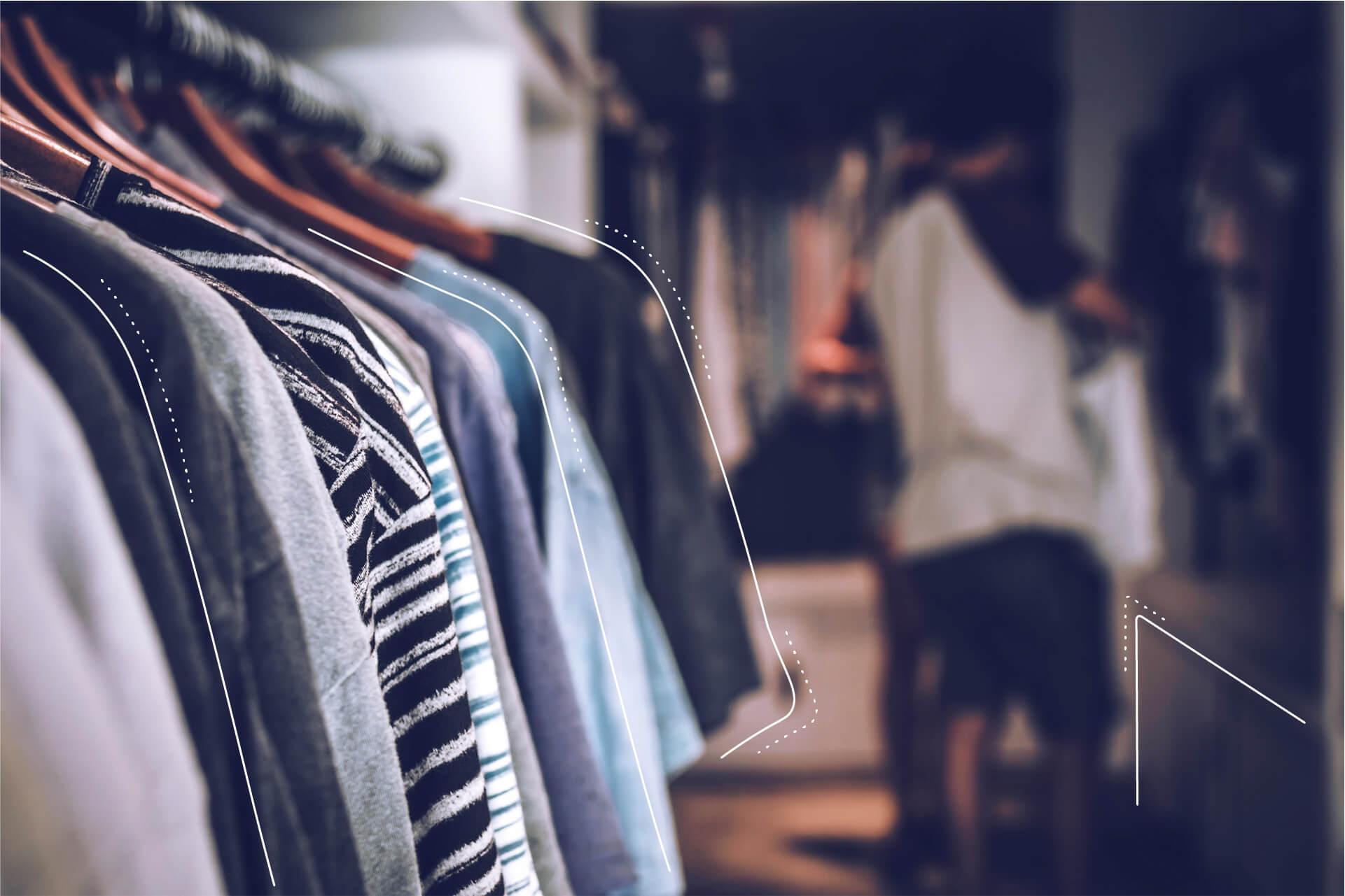 Eine unscharf Dargestellte Kleiderstange mit T-Shits und einer Person im Hintergrund. | eggheads.net